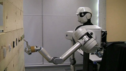 Image of the humanoid robot pressing a doorbell button.